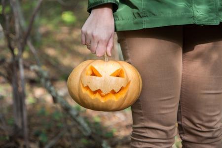 jack o' lantern: Woman in autumn garden holding Halloween pumpkin Jack o lantern