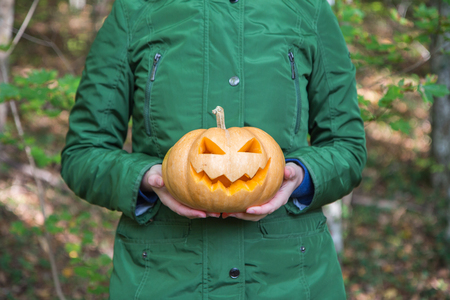 Woman in autumn forest with Halloween pumpkin Jack o lantern in his hand Stock Photo