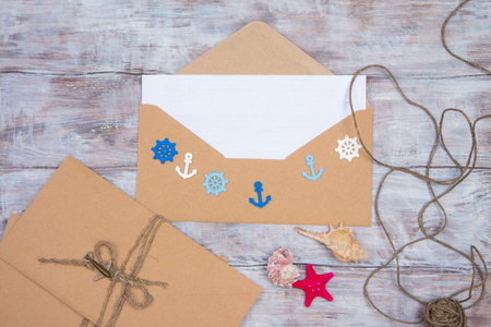 embellishments: Envelope with blank sheet of paper and embellishments in nautical theme - steering wheel, anchors, shells and starfish. Space for your text