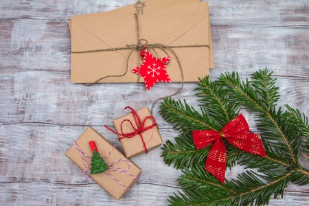 Fir branch, envelopes, Christmas gifts and letters on a wooden background.