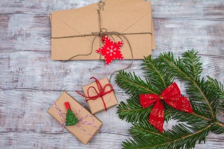 Jednoduchá větev, obálky, vánoční dárky a dopisy na dřevěném pozadí.