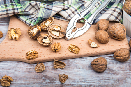 Walnuts, nutcracker and checkered towel on cutting board. Wooden background