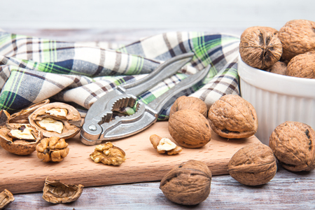 Walnuts, nutcracker on cutting board, checkered towel and white ceramic bowl. Wooden background