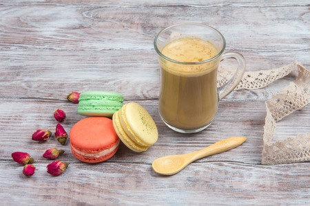 Cup of coffee, French pastries macaron and dried flower buds of rose on gray wooden background
