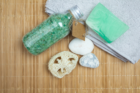 Set spa: handmade soap, bath salts, loofah, stones and towel on a bamboo mat background. Top view.