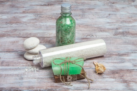 Sea salt, aromatic handmade soap, stones and shell on wooden background. Spa and wellness