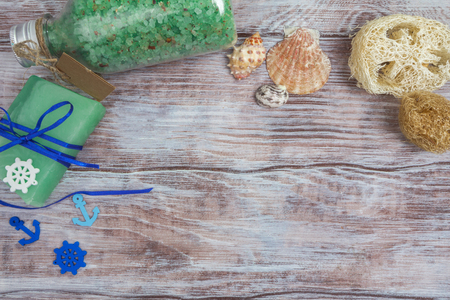 Spa set with sea salt bath, natural handmade soap, a loofah, and seashells decorated in a marine style. Space for your text