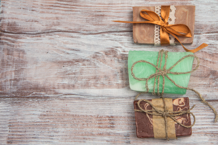 Set of three natural soaps of different colors on a wooden background. Space for your text. Top view