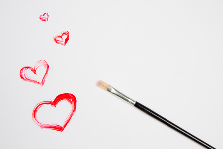 Heart drawn with red paint on white sheet of paper and brush.