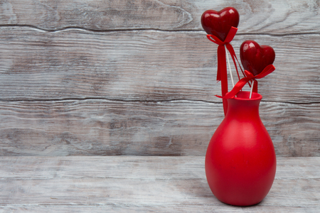 gray: Red ceramic vase and hearts on stick. Gray rustic wooden background.