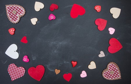 hilo rojo: Red and pink hearts on a black chalkboard. Space for your text. Ornaments for Valentines Day or wedding Foto de archivo