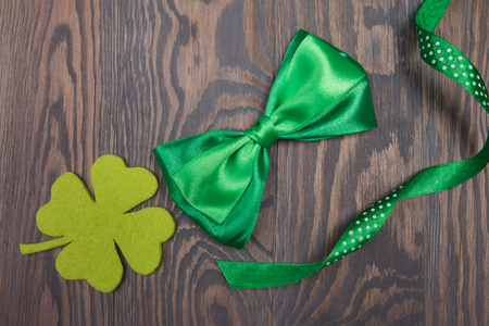 Quarterfoil clover and green bow tie on wooden brown background. St. Patrick s Day. Traditional Irish symbols and decoration