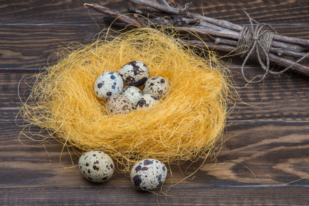 Nest of sisal with quail eggs on wooden rustic table. Easter background
