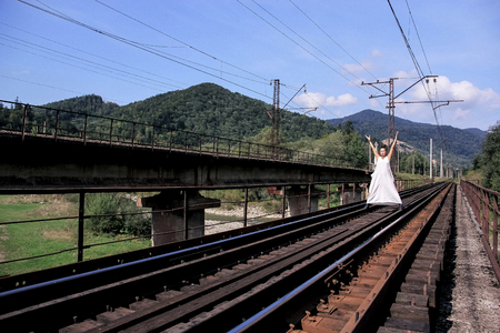 Brunette in a long beautiful white dress. Railway in the mountains of Georgia. Nature of Georgia. A young woman stands on iron rails and sleepers.way home. Railway.