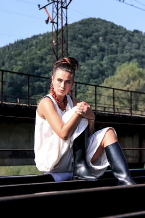 A young woman is sitting on the rails in a white dress. Attractive girl in a white dress and black boots. A lady in a white dress is sitting on a background of green mountains. 스톡 콘텐츠