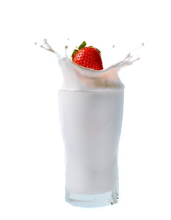 splashing strawberry into a milk glass photo