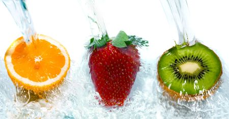 Fresh fruit jumping into water with a splash Stock Photo