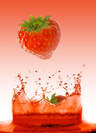Strawberry falling in juice. Isolation.  Stock Photo