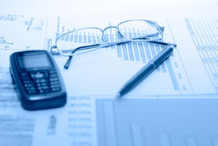 bluelines: Business accessories on a background of diagrams Stock Photo