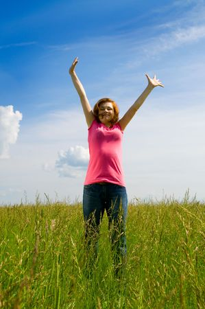 spreading arms: beautiful spreading her arms in the middle of a field Stock Photo
