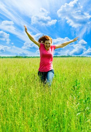 beautiful spreading her arms in the middle of a field Stock Photo