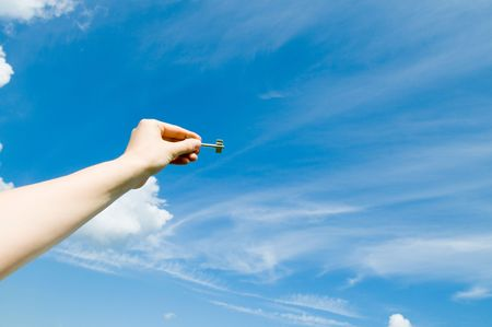 hand holding keys,blue skies in the background Stock Photo