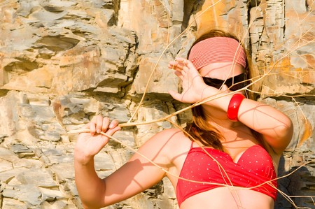 beautiful woman in a bathing suit against rocks photo