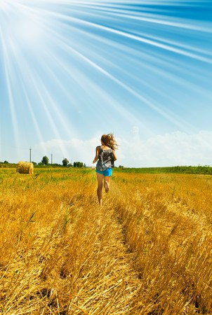 Harvest, girl throwing grass on background of the sky photo