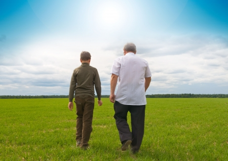 sons and grandsons: grandson and  grandfather in the field Stock Photo