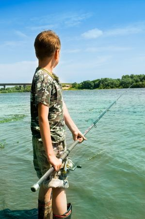 Ni�o pescando en el lago Foto de archivo - 5660539