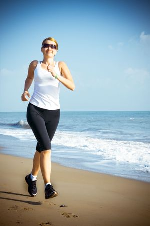 young woman jogging on the beach Stock Photo