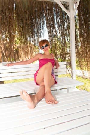 girl in pink dress on bench on beach photo