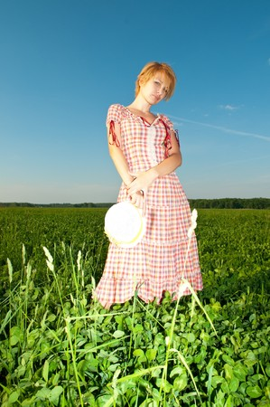 young beautiful woman on field in summer photo