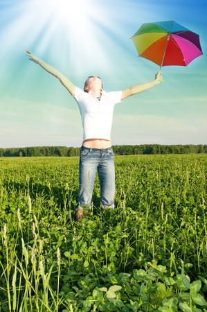 girl under blue sky with umbrella in  field photo