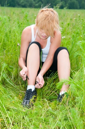 fastens: young woman fastens laces on trainers.
