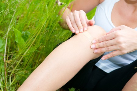 young woman with foot trauma in  field. Stock Photo