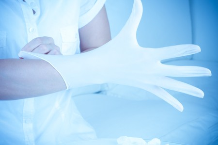 Pulling on surgical glove Stock Photo - 7499279