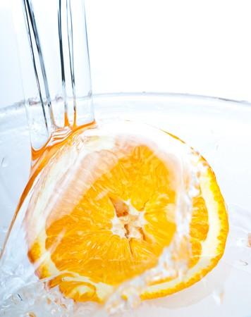 orange into water splash on white photo