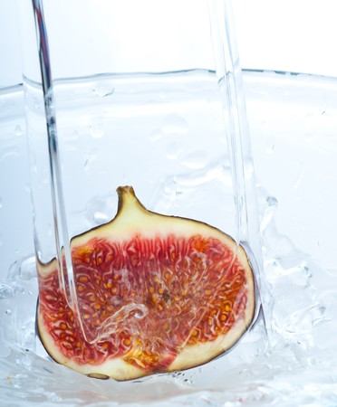 fig into water splash on white photo