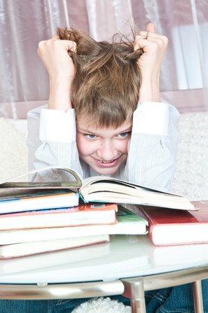 pupil sits at  table with books photo