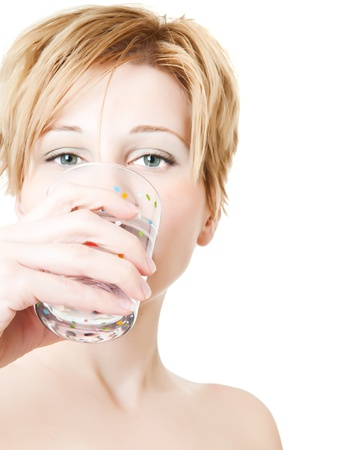 Beautiful young woman drinks water from glass photo