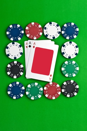 Counters and playing cards on a green background photo