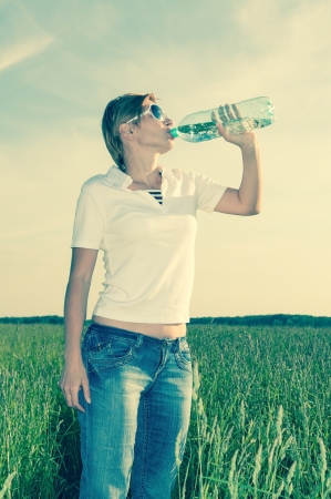 young woman with a bottle of water on the field photo