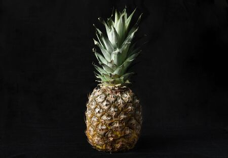 whole pineapple on a black background.Close-up