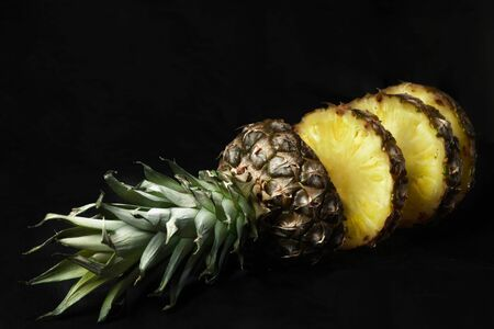 ripe pineapple cut into pieces on a black background