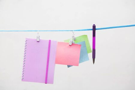 colored stickers with on clothespins on a white background with copy space