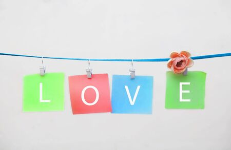 colored stickers with the words love on clothespins on a white background with copy space