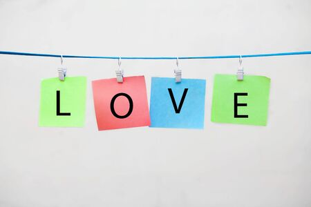 colored stickers on clothespins with the words love on a white background Banque d'images