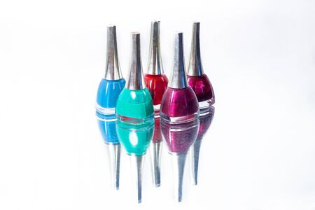 set of nail polishes on a reflective surface