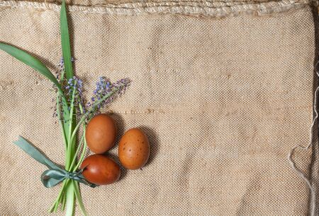 Easter eggs and a bouquet of flowers on a natural linen background Banque d'images